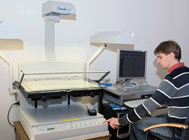 Specialist A. Mazalas is scanning a publication with Bookeye scanner. © D. Mukienė